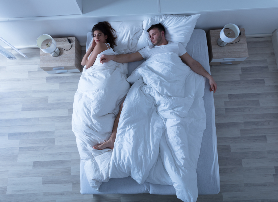 couple sleeping in bed, but man is taking it over from the woman