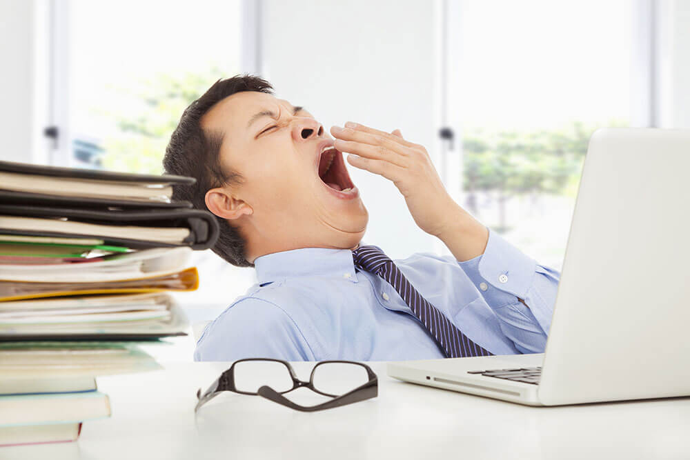 Man-Yawning-at-Work with pile of books and computer